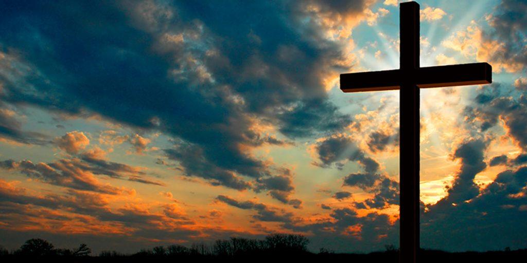 Cruz no fim de tarde com luz brilhando atrás